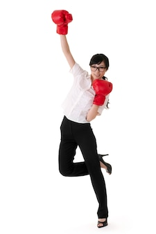 Cheerful business woman raise up hands with red boxing gloves