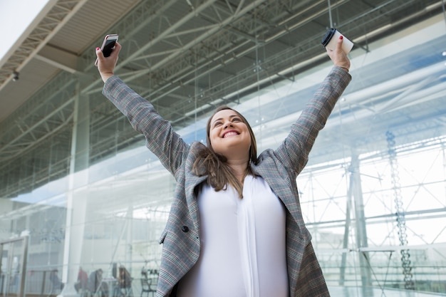 Cheerful business woman raising arms outdoors