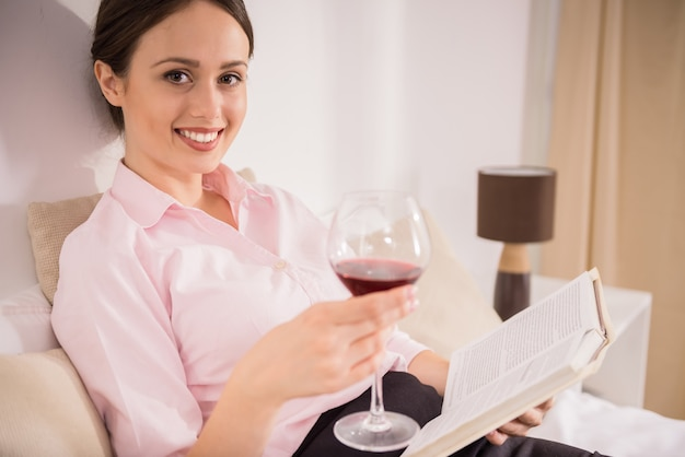 Cheerful business woman reading a book, holding glass.