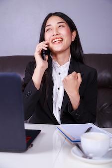 机に座って携帯電話で話す朗らかなビジネス女性