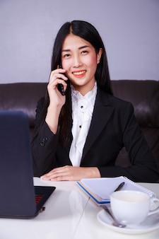 Cheerful business woman sitting at the desk and talking on mobile phone