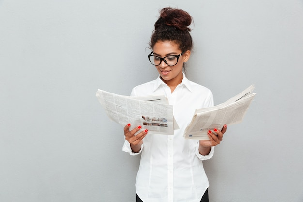 Cheerful business woman standing over grey wall with newspapers