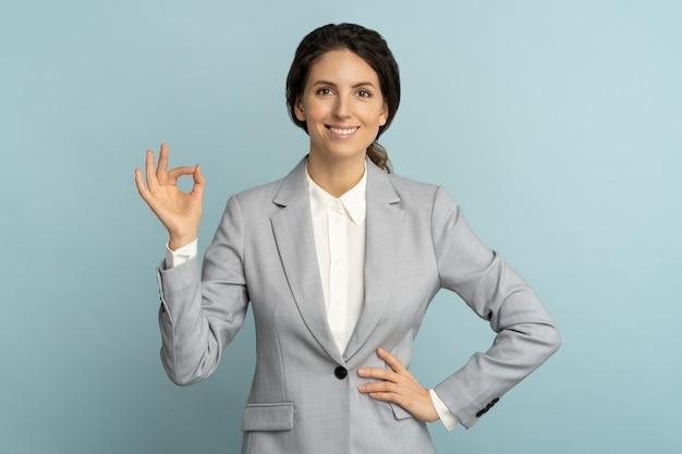 쾌활 한 비즈니스 여자는 스튜디오 파란색 배경 위에 확인 표시를 보여주는 광범위 하 게 웃 고 좋은 분위기에서 재킷을 착용합니다. 긍정적 인 사무실 직원 여성이 제품을 광고합니다. 고객, 판매, 할인.