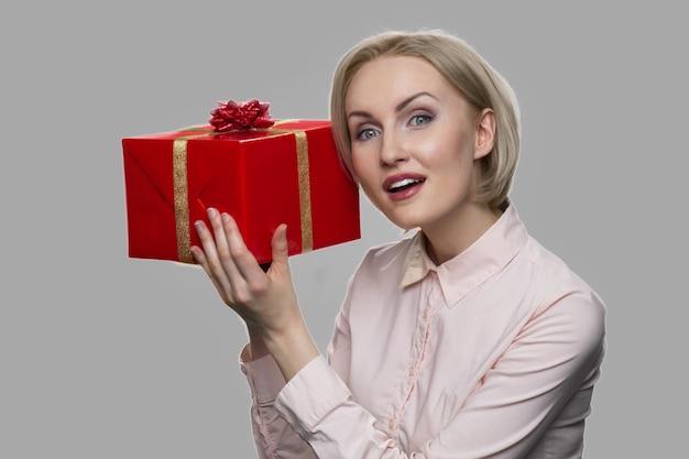 선물 상자와 쾌활 한 비즈니스 우먼입니다. 회색 배경에 현재 상자를 들고 젊은 흥분된 여자. 여자를 행복하게 만드는 법.
