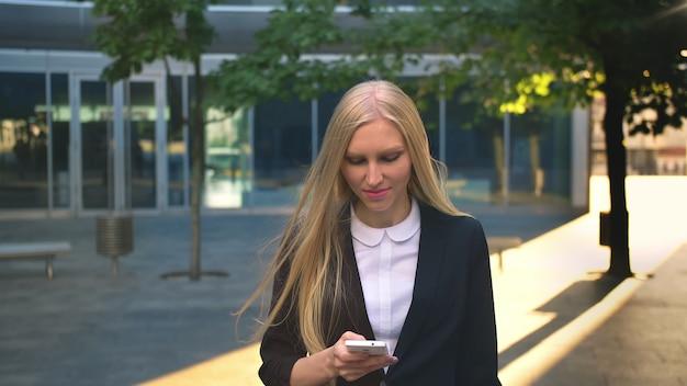 Веселый бизнес женщина с телефона на открытом воздухе. довольная белокурая девушка в черном пиджаке держит смартфон и смотрит в сторону с улыбкой на улице