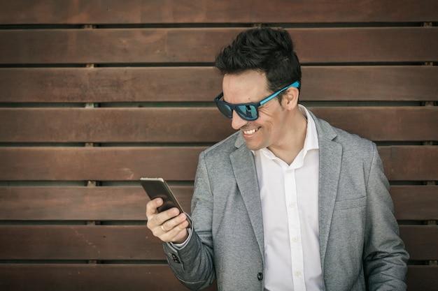 Веселый бизнесмен, просматривающий мобильный телефон