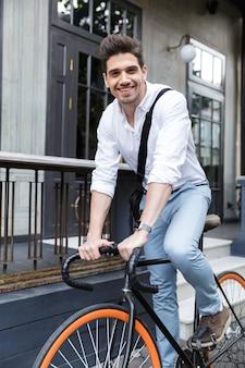 Веселый бизнесмен, одетый в рубашку, езда на велосипеде