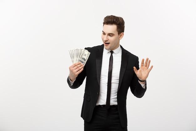 회색 배경에 달러 지폐를 들고 있는 쾌활한 사업가입니다.