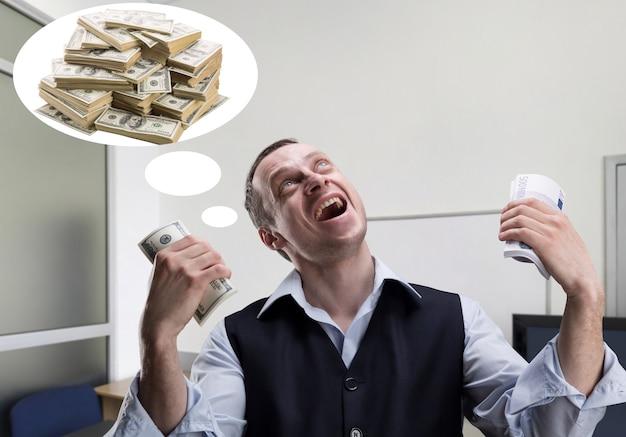 Веселый бизнесмен держит деньги и мечтает в офисе
