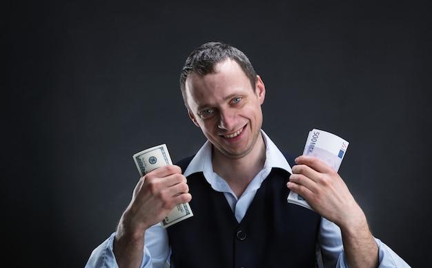 Веселый бизнесмен держит деньги в обеих руках