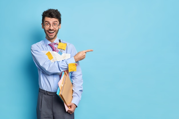 Cheerful businessman holds papers with diagrams and formulas dressed in formal clothes indicates happily away on blue space gives recommendation how to prepare financial report. man analyst indoor