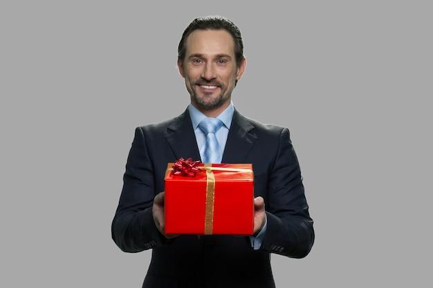 ギフトボックスを提供する陽気なビジネスマン。灰色の背景にギフトボックスを提示するハンサムなビジネスマン。ホリデーセールのコンセプト。
