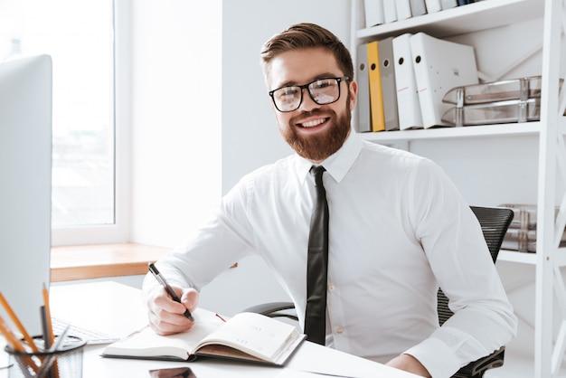 ノートを書きながらオフィスに座っている陽気なビジネスマン