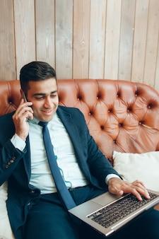 オフィスでラップトップと一緒に座っている陽気なビジネスマン