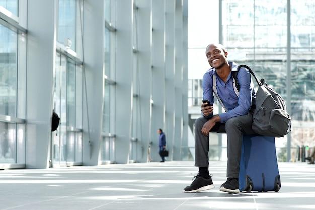 荷物と携帯電話で駅に座って明るい実業家