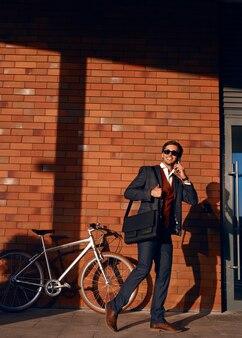 스마트 폰 자전거 근처에 말하는 쾌활 한 사업가