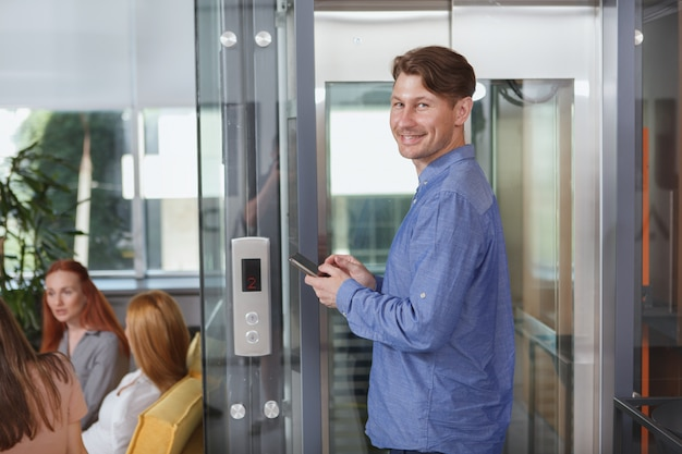 Веселый бизнесмен с помощью смартфона в ожидании лифта в офисном здании