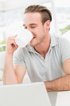 Cheerful businessman using laptop while drinking