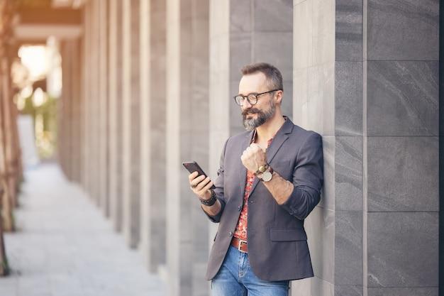 Веселый бизнесмен с помощью мобильного телефона и кричать от радости в городе
