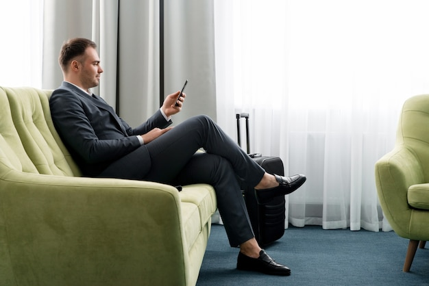 Cheerful businessman using phone sitting in hotel room with suitcase on business trip