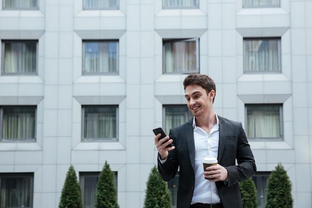 Веселый бизнесмен с помощью смартфона