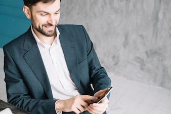 Cheerful businessman using smartphone