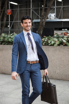 Cheerful businessman walking on street