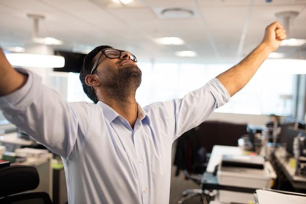 Веселый бизнесмен с поднятыми руками в офисе