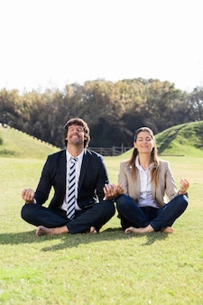 Cheerful businesspeople in the lotus position