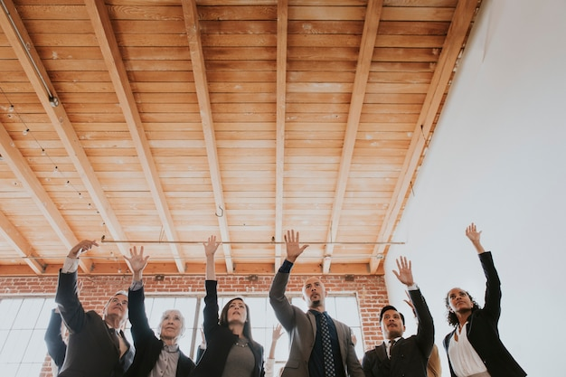 Cheerful businesspeople raising hands in the air