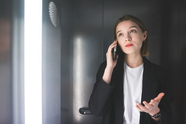 Cheerful businesswoman explaining something by the phone in the elevator wearing smart black suit.