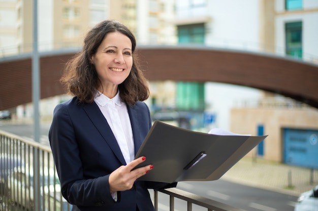 Cheerful businesswoman holding folder