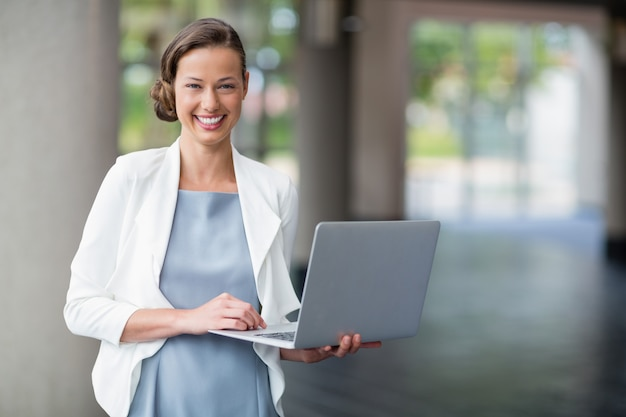 Cheerful businesswoman holding laptop at conference centre