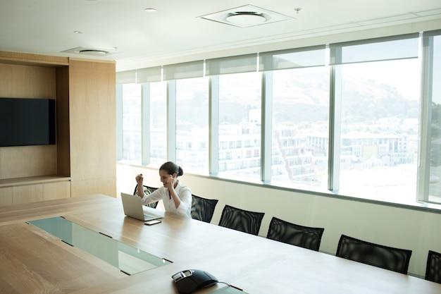 オフィスに座っている陽気な女性実業家