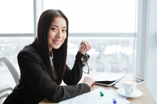 Cheerful businesswoman sitting and holding glasses at table in office