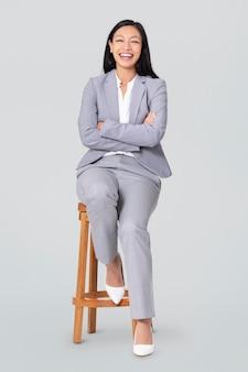 Donna d'affari allegra seduta su uno sgabello di legno lavori e campagna di carriera