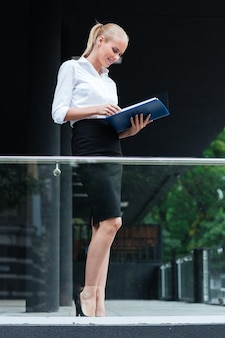 Cheerful businesswoman standing with folders at the glass balcony outdoors