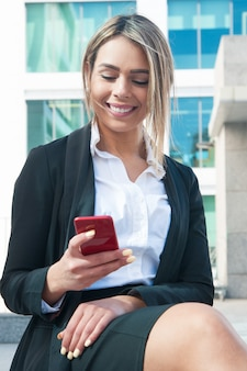 Cheerful businesswoman texting on phone outdoors