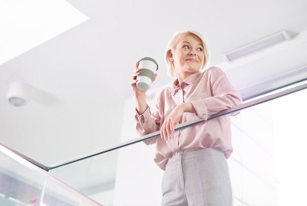 Веселая деловая женщина с кружкой кофе, опираясь на перила