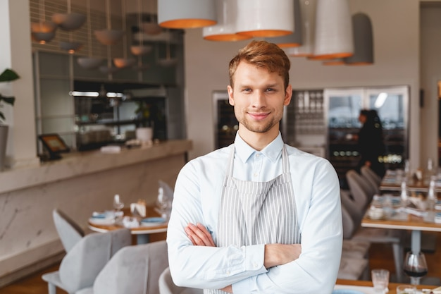 Cheerful cafe worker with crossed arms looking and smiling