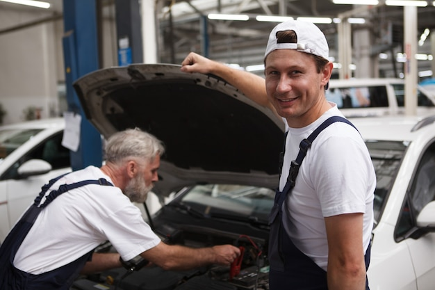 先輩と一緒に車の作業をしながらカメラに微笑む元気な自動車整備士