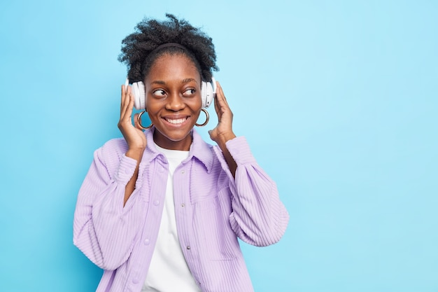 Cheerful carefree dark skinned woman with curly hair keeps hands on stereo headphones