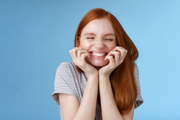 Cheerful carefree giggling ginger girl look happy bright close eyes smiling delighted hold hands cheeks having fun feeling excitement joy triumphing cheering good news, standing blue background