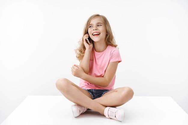 Веселая беззаботная счастливая белокурая европейская маленькая девочка-подросток ведет забавную забавную беседу, расслабленно сидит, скрестив ноги, на полу, разговаривает со смартфоном, радостно смеется, позирует у белой стены