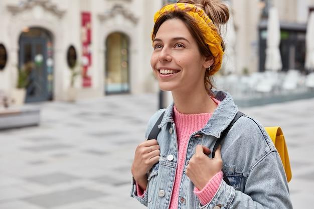Donna allegra e spensierata vestita con abiti alla moda, ha un sorriso affascinante sul viso, gode del tempo libero, trasporta un piccolo zaino