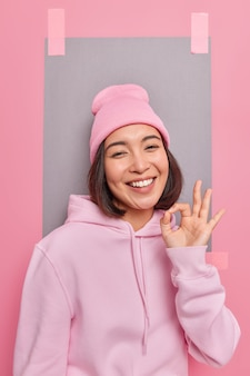 Cheerful carefree woman shows okay gesture in approval demonstrates recommendation sign agrees with you praises good work wears hoodie and hat poses indoor