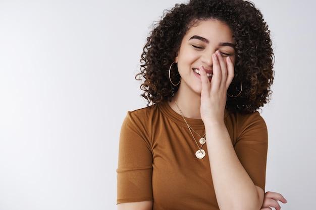 Веселая беззаботная молодая позитивная кудрявая стильная девушка смеется искренними закрытыми глазами прикрывает белые зубы ладонь хихикает смешная шутка стоит радостная белая стена
