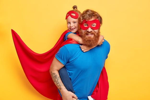 陽気な思いやりのある父は小さな娘と遊ぶ英雄的な子供に便乗を与える