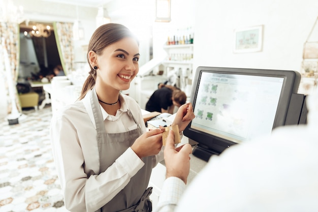Cheerful cashier using digital device for payment