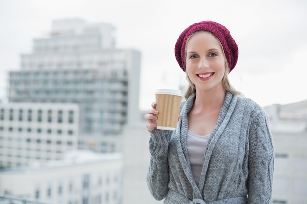 Cheerful casual blonde holding coffee outdoors